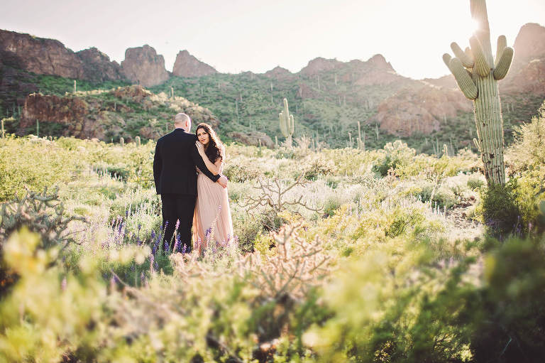 Standing in the sunlight amongst the wildflowers, the Paxman's hold one another during their couple's session at Picacho Peak