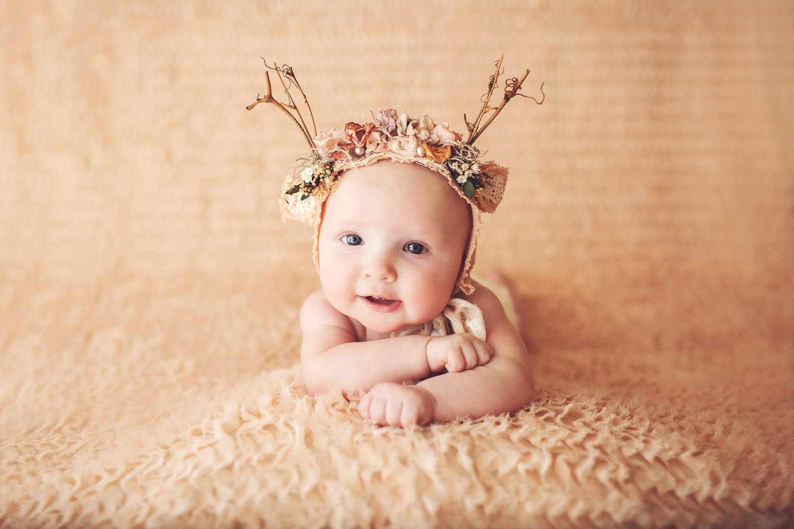 Three-month old baby girl in a peach, floral deer bonnet during her milestone session