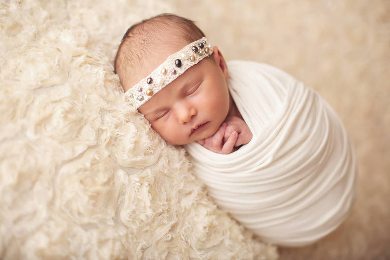 A sleeping beauty during her newborn session. The wrap helped her calm and stay asleep during her session.